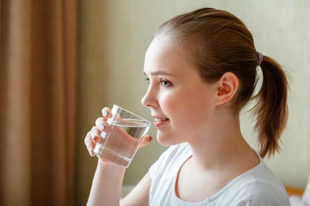 Happy teen girl hält den wasserhaushalt für die körpergesundheit aufrecht, indem es eine transparente tasse sauberes wasser trinkt lächelnde junge frau trinkt morgens nach dem aufwachen ein glas reines wasser.