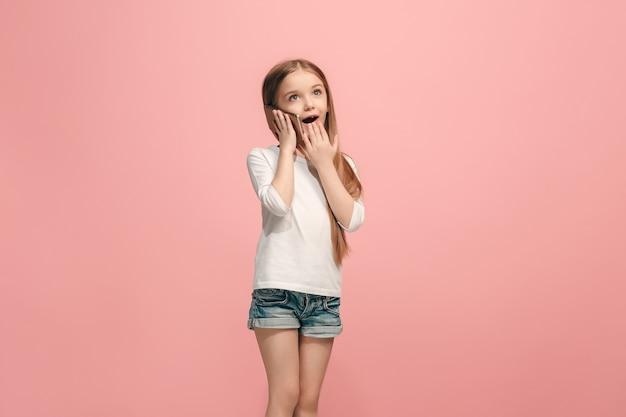 Happy teen girl stehend, lächelnd mit handy über trendige rosa wand. schönes weibliches brustbild. menschliche emotionen, gesichtsausdruckkonzept.