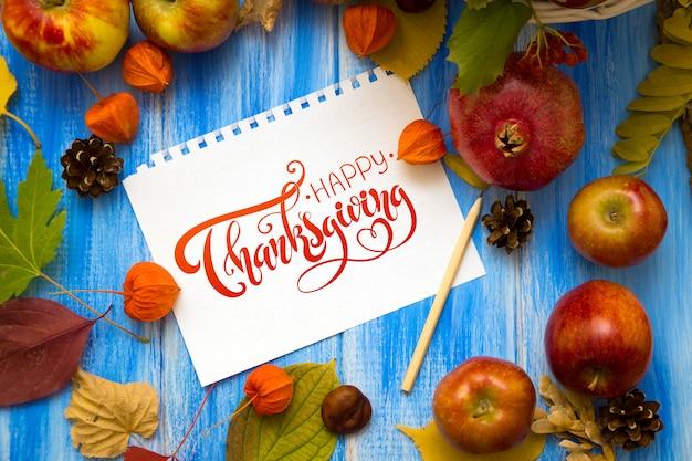 Happy thanksgiving day grußkarte - handschriftliche inschrift. blätter und früchte