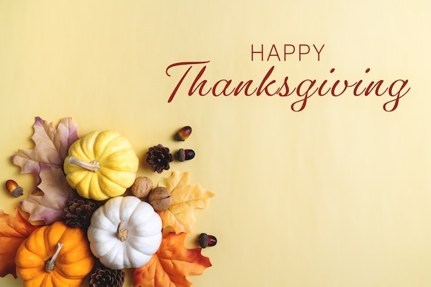 Happy thanksgiving day mit kürbis und nuss auf gelbem hintergrund
