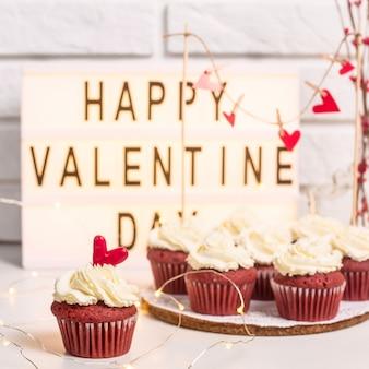 Happy valentine's day steht auf einer dekorativen lampe neben roten cupcakes