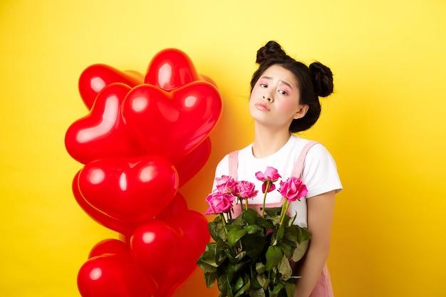 Happy valentines konzept. traurige und düstere asiatische frau, die rosenstrauß hält und sich verärgert fühlt