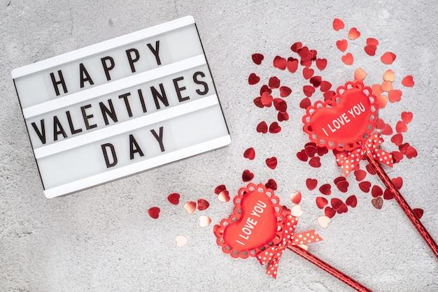 Happy valentinstag lichtbox mit rotem glitzer und dekorativen stoffherzen auf stöcken