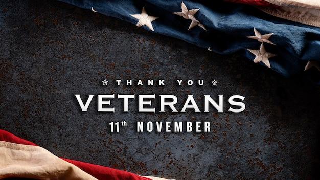 Happy veterans day konzept. amerikanische flaggen gegen einen dunklen steinhintergrund