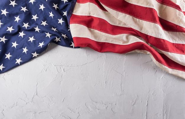 Happy veterans day konzept. amerikanische flaggen gegen einen weißen steinhintergrund. 11. november.