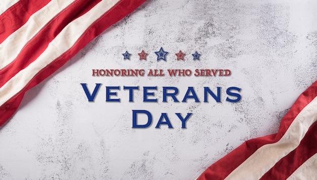 Happy veterans day konzept. amerikanische flaggen vor einem dunklen steinhintergrund. 11. november.
