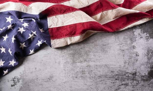 Happy veterans day konzept amerikanische flaggen vor einem dunklen steinhintergrund