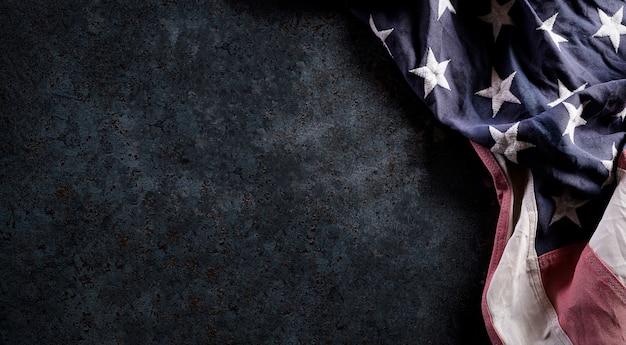 Happy veterans day konzept. vintage amerikanische flaggen gegen dunklen steinhintergrund