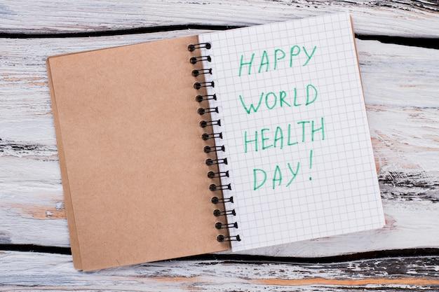 Happy world health day konzept. geöffneter notizblock mit wünschen. weißer holztisch.