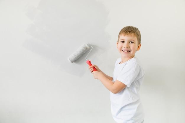 Happysmoling kleinkind kind malerei wand .. das konzept des umzugs in eine neue wohnung. netter kleiner junge, der wand in seinem zimmer malt.