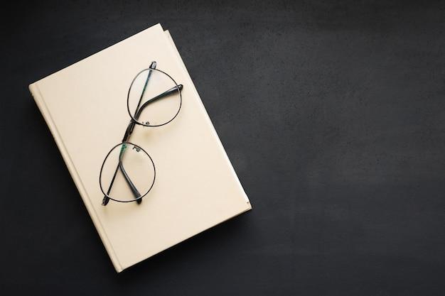 Hardcover beige buch und lesebrille auf schwarzem schieferbrett.
