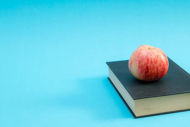 Hardcover-buch mit und rotem apfel auf blauem hintergrund.