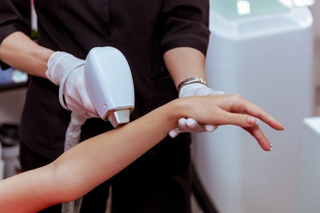 Hardware-haarentfernungsverfahren am körper des mädchens eine kosmetikerin führt eine laser-haarentfernung durch