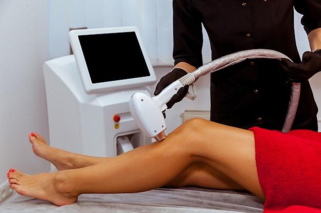 Hardware-haarentfernungsverfahren am körper des mädchens. eine kosmetikerin führt in einem schönheitssalon eine laser-haarentfernung am bein durch. hautpflege, hardware-kosmetologie.