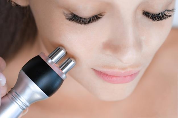 Hardware-kosmetologie. junge frau, die rf-facelifting-verfahren im schönheitssalon erhält.