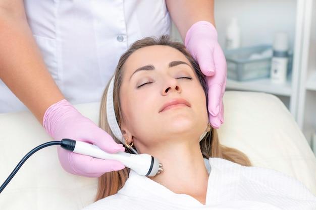 Hardware-kosmetologie. schließen sie herauf bild der reizenden jungen frau mit den geschlossenen augen, die hf-hebeprozedur im schönheitssalon erhalten.