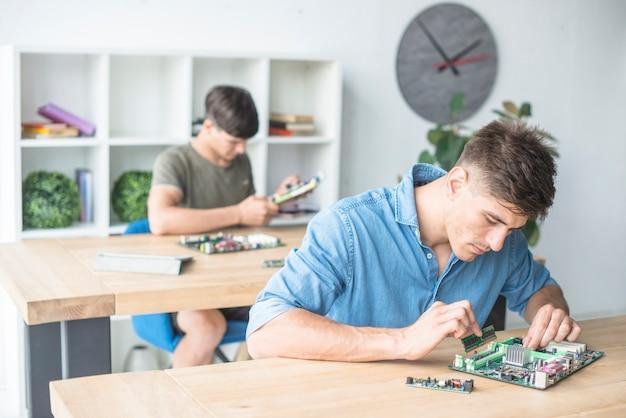Hardwaretechnikerstudenten, die mit computerkomponenten üben