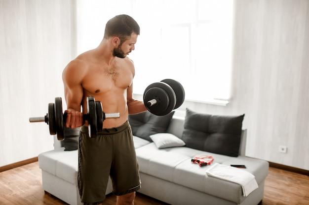Hardwoking t-shirtless typ sportler stehen auf dem boden und halten hanteln in der hand. bereit zum training. gewöhnliche menschen arbeiten daran, seinen körper zu verbessern.