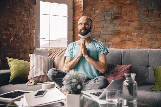 Harmonie. junger mann, der zu hause yoga macht, während er unter quarantäne steht und freiberuflich online arbeitet