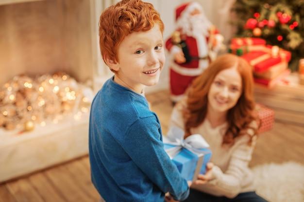 Harmonische beziehungen. selektiver fokus auf einen charmanten ingwerjungen mit aufgeregten augen und weihnachtsgeschenk für ihre mutter.
