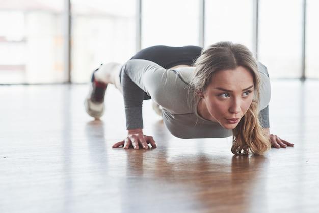 Hart arbeitend. sportliche junge frau haben fitness-tag im fitnessstudio zur morgenzeit