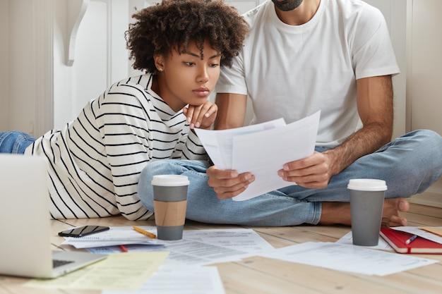 Hart arbeitende interracial-marketing-experten posieren auf dem boden, studieren die dokumentation und erstellen einen monatlichen bericht
