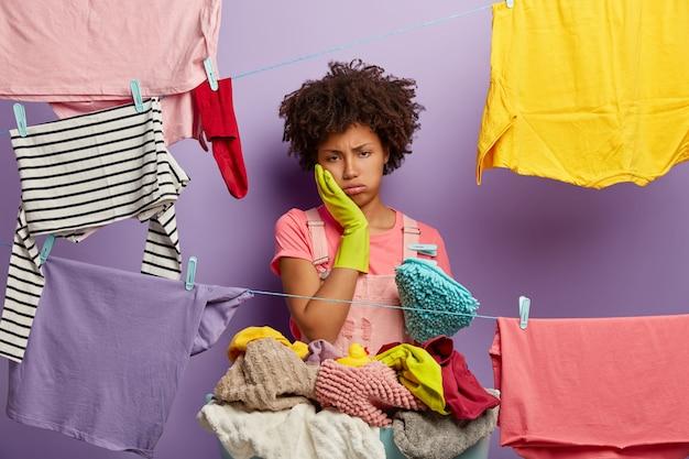 Hart arbeitende müde hausfrau seufzt vor müdigkeit, berührt die wange, trägt gummihandschuhe, steht in der nähe von wäscheleinen mit aufgehängter sauberer kleidung, langweilt sich vom alltag zu hause, wäscht den ganzen tag