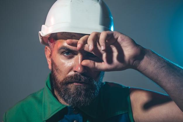 Hart arbeitender baumeister, der mit bauhelmporträtarchitektbauer auf der baustelle arbeitet