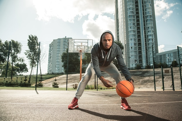 Hart arbeitender mann. netter angenehmer mann, der zum basketballplatz kommt, während er trainiert, um gut basketball zu spielen