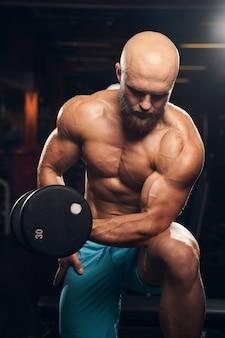 Hart arbeitender, muskulöser mann, der gewichte hebt, während er im fitnessstudio trainiert