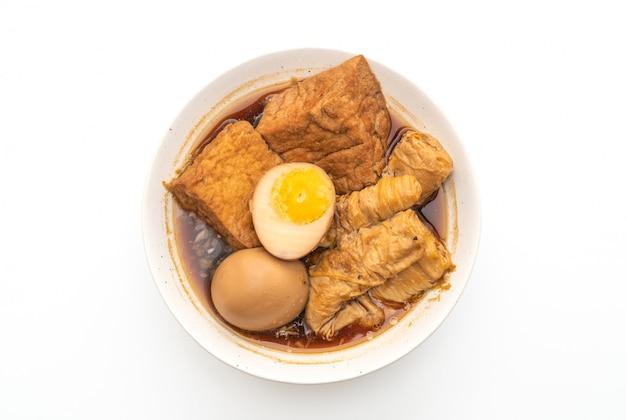 Hart gekochtes ei in brauner soße oder süßer soße isoliert auf weißem hintergrund