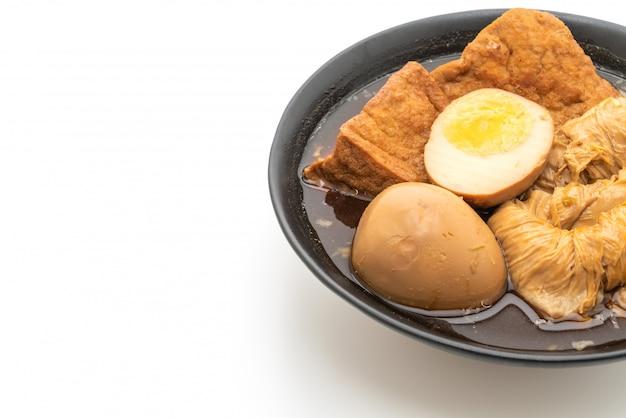 Hart gekochtes ei in der braunen soße oder in der süßen soße lokalisiert auf weißem hintergrund