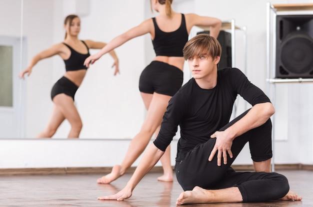 Harte arbeit und ausdauer. hübscher junger professioneller tänzer, der auf dem boden sitzt und sein bein berührt, während er mit seinem tanzpartner trainiert