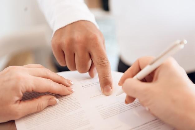Harte männliche hand zeigt mit dem finger, wo sie unterschrift setzen soll.