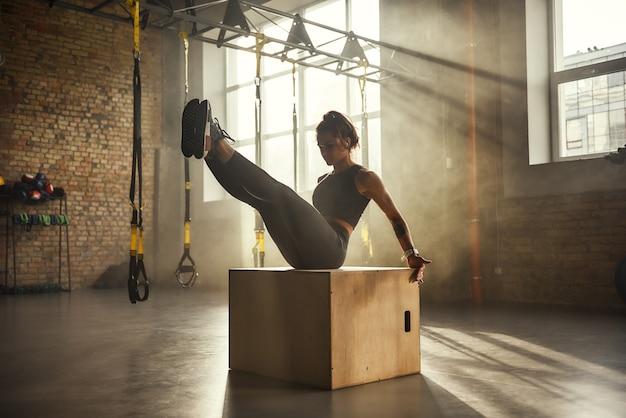 Harte seitenansicht einer sportlichen frau in sportbekleidung, die beine im fitnessstudio trainiert