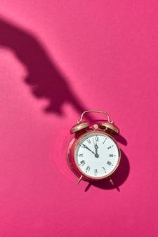 Harter schatten von weiblicher hand drückt auf altmodischen cooper gemalten wecker auf einem heißen rosa hintergrund mit kopienraum.