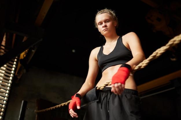 Harter weiblicher boxer, der kamera betrachtet