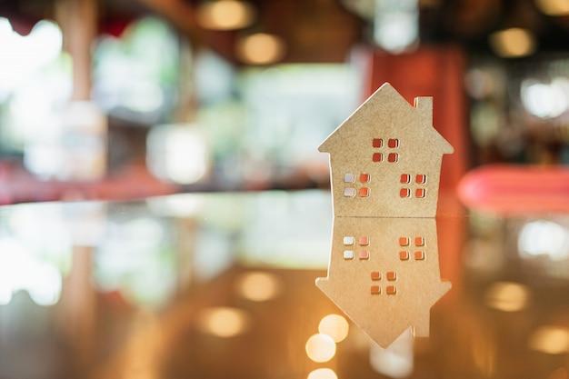 Hartes papierhaus auf dem tisch, ein symbol für bau