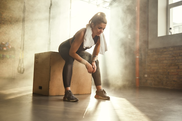 Hartes training müde athletische frau mit perfektem körper in sportkleidung mit handtuch auf ihr