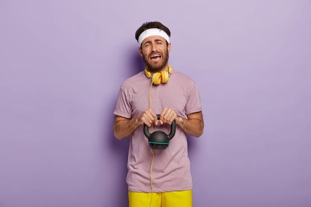 Hartes trainingskonzept. der traurige, unglückliche junge mann hebt schweres gewicht, ist demotiviert für den sport, hat keine lust, im fitnessstudio zu arbeiten, trägt ein weißes stirnband, freizeitkleidung und hört musik während des trainings