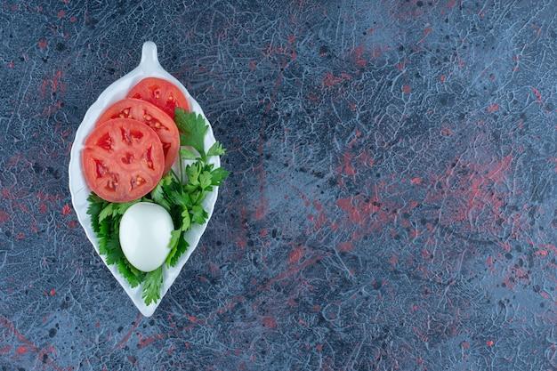 Hartgekochtes ei mit geschnittenen tomaten und kräutern