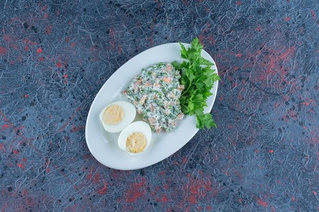Hartgekochtes ei mit salat auf weißer tiefer schüssel.
