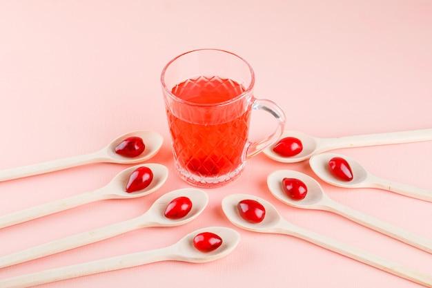 Hartriegelbeeren in den hölzernen löffeln mit trinken hohe winkelansicht auf rosa