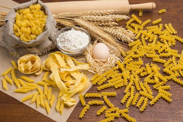 Hartweizennudeln. eier und mehl, nudelholz und weizenzweige auf dem tisch