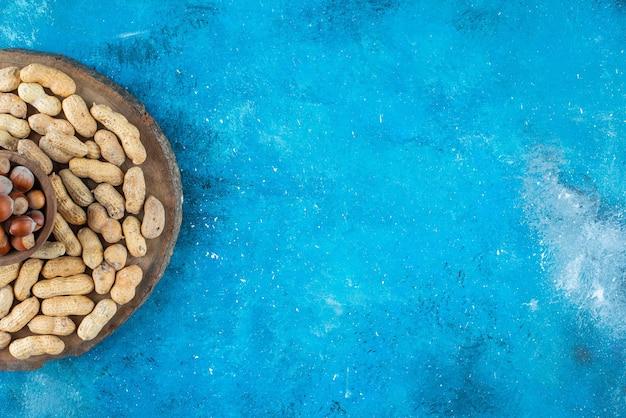 Haselnüsse in einer schüssel an bord mit erdnüssen, auf dem blauen tisch.