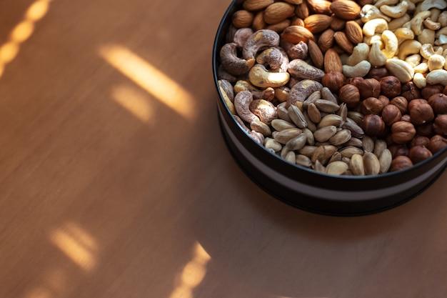 Haselnüsse, mandeln, rohe cashewnüsse, gebratene cashewnüsse und pistazien in teller auf holztisch.