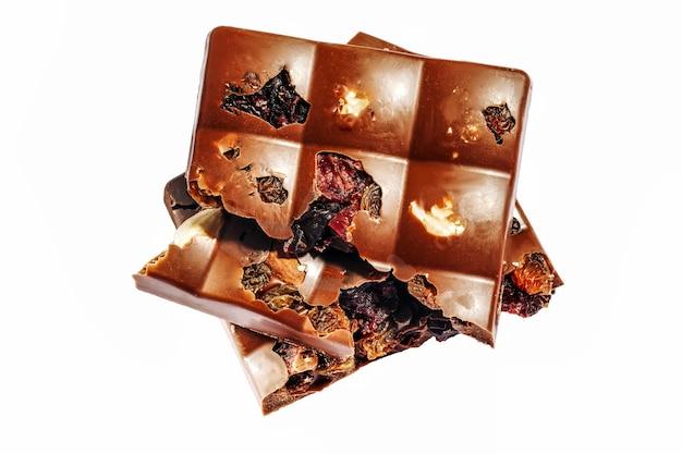 Haselnuss und getrocknete früchte dunkle schokoladenstücke turm isoliert auf weiss.