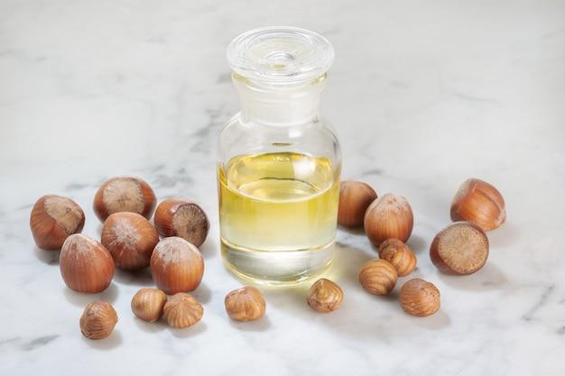 Haselnussöl in glasflasche auf marmortisch. öl für kosmetik- oder schönheitspflege