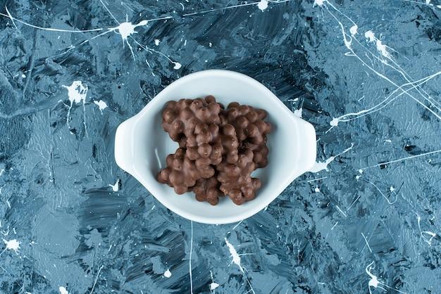 Haselnussschokolade in einer schüssel auf dem blauen tisch.