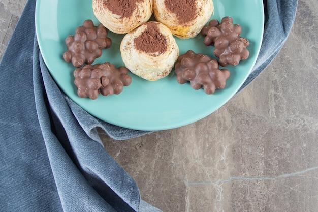 Haselnussschokolade und kakaopulver auf keksen auf einem teller auf handtuch auf blau.